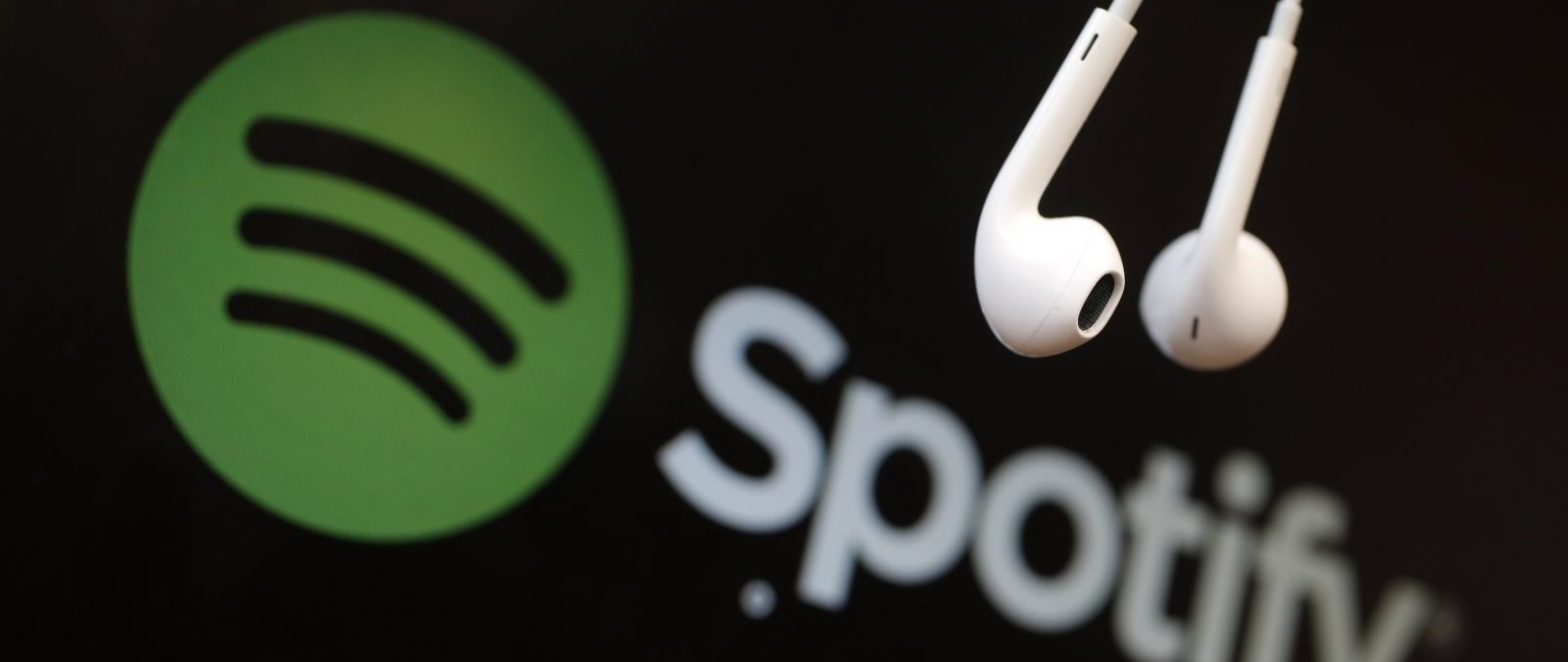 Headphones are seen in front of a logo of online music streaming service Spotify in this illustration picture